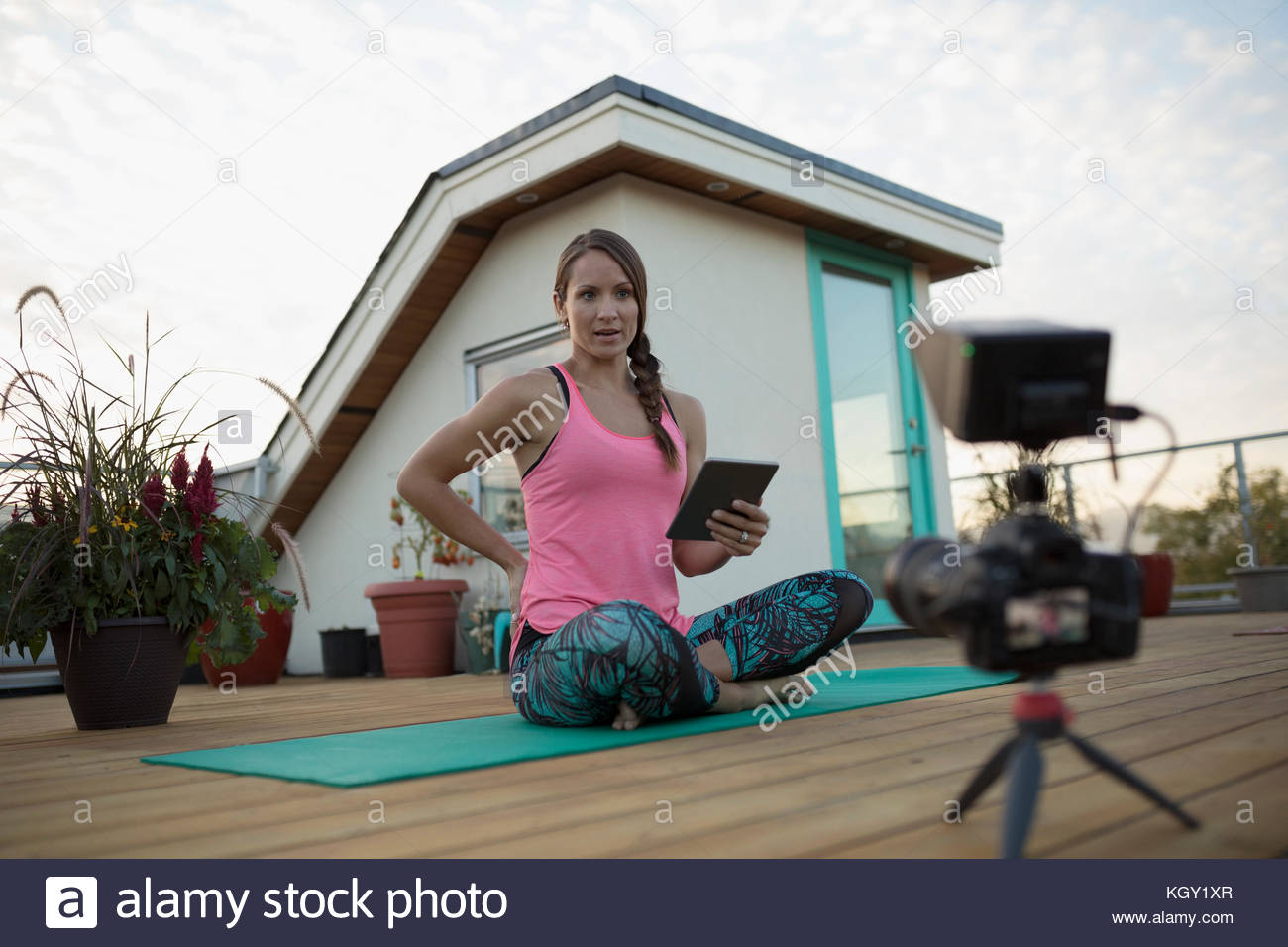 Female yoga instructor with digital tablet and video camera filming, vlogging on yoga mat on deck patio - Stock Image