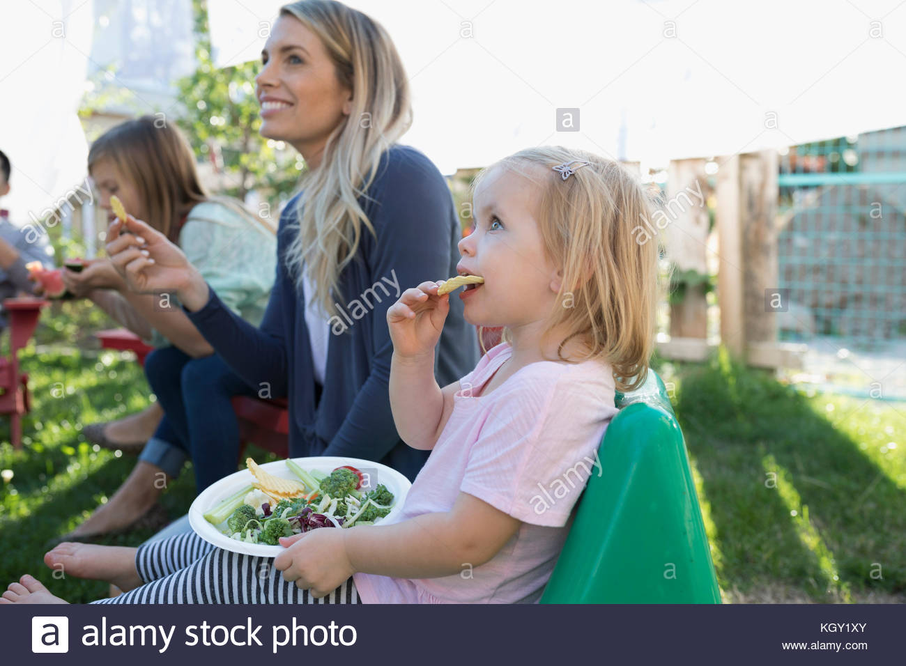 Mother and toddler daughter eating at backyard barbecue - Stock Image
