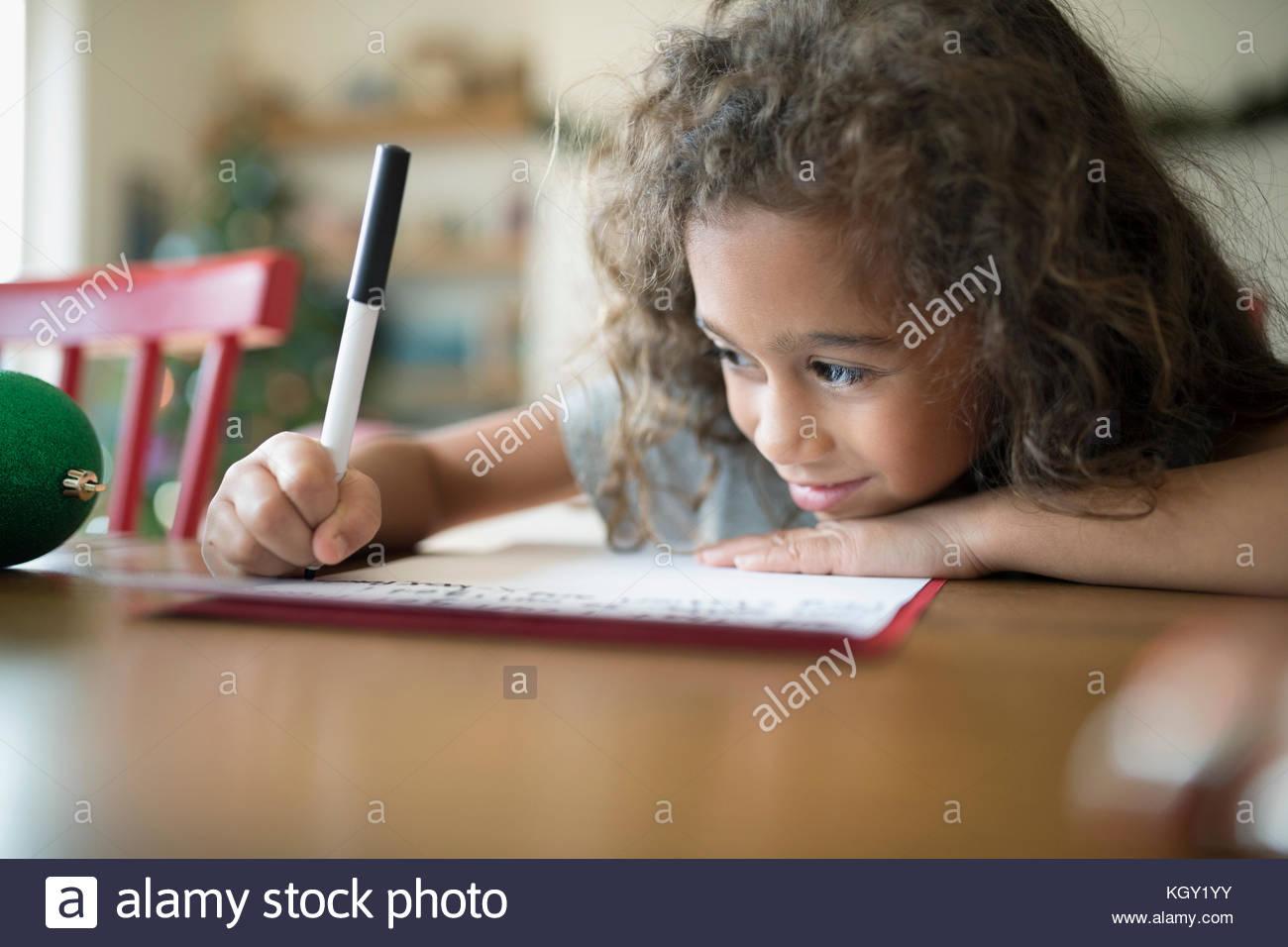 Smiling girl writing Christmas letter to Santa at table - Stock Image