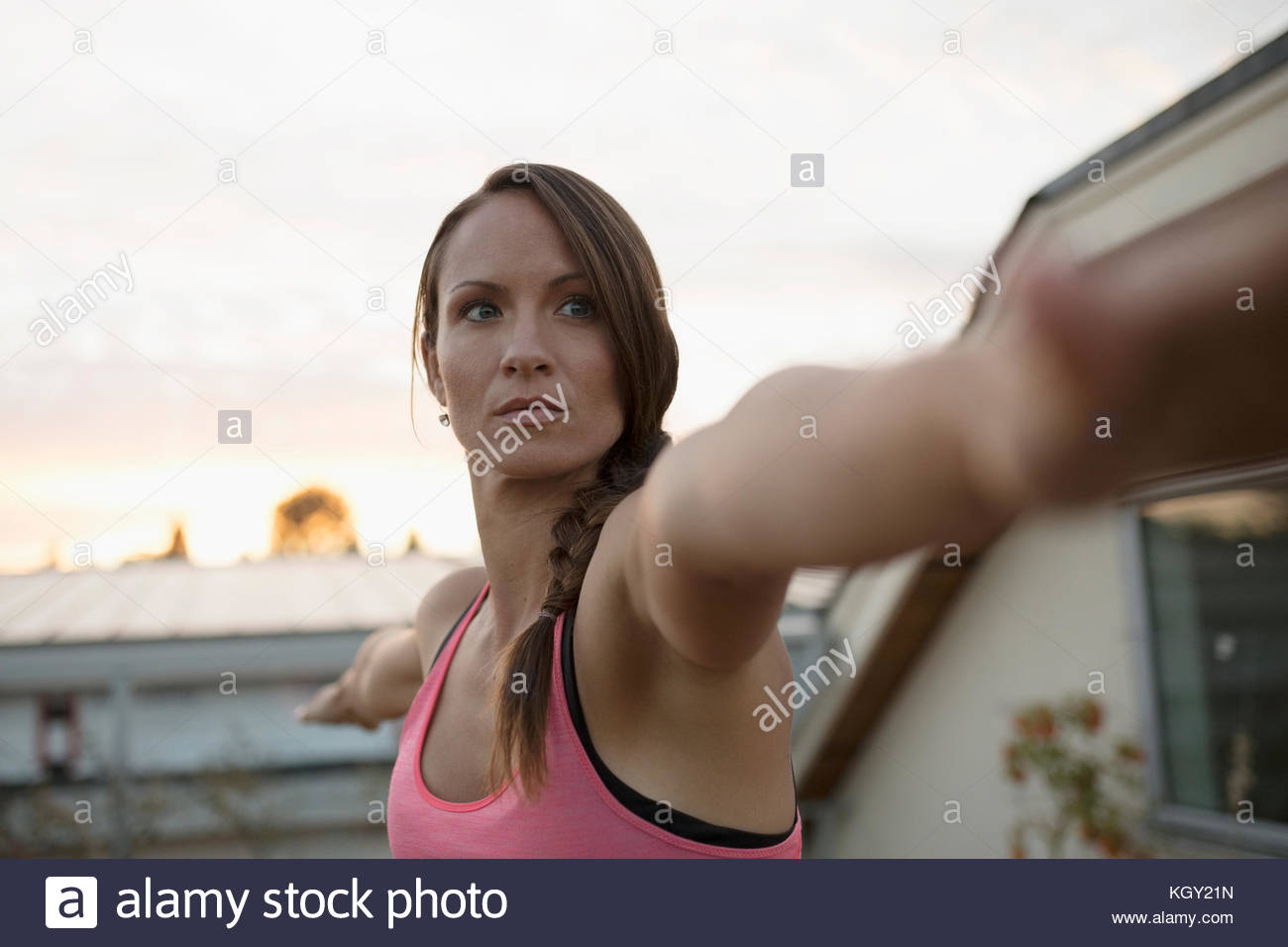 Serious, focused woman practicing yoga warrior 2 pose with arms outstretched - Stock Image
