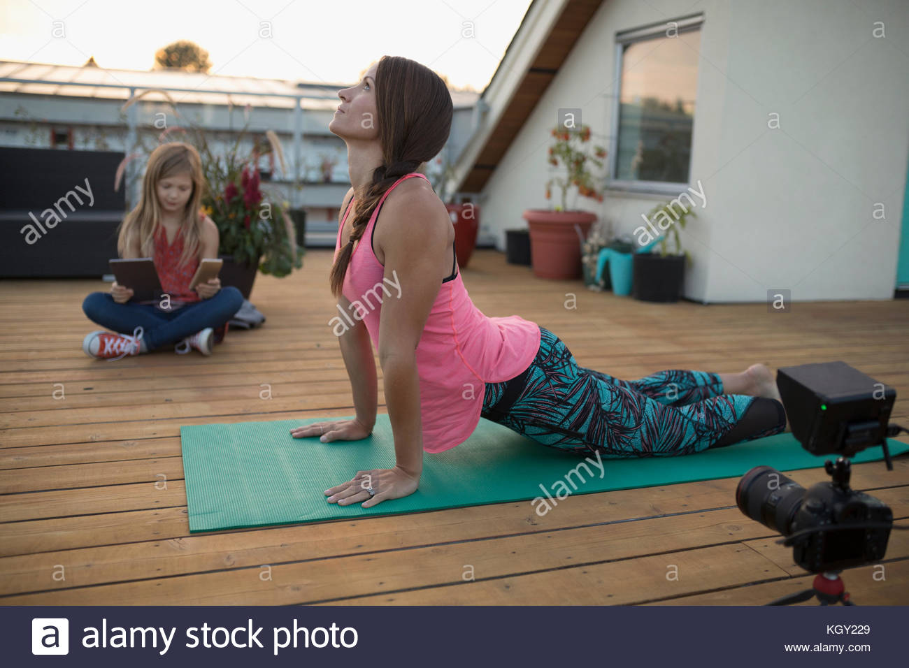 Female yoga instructor with video camera filming, vlogging upward facing dog yoga pose on patio deck - Stock Image