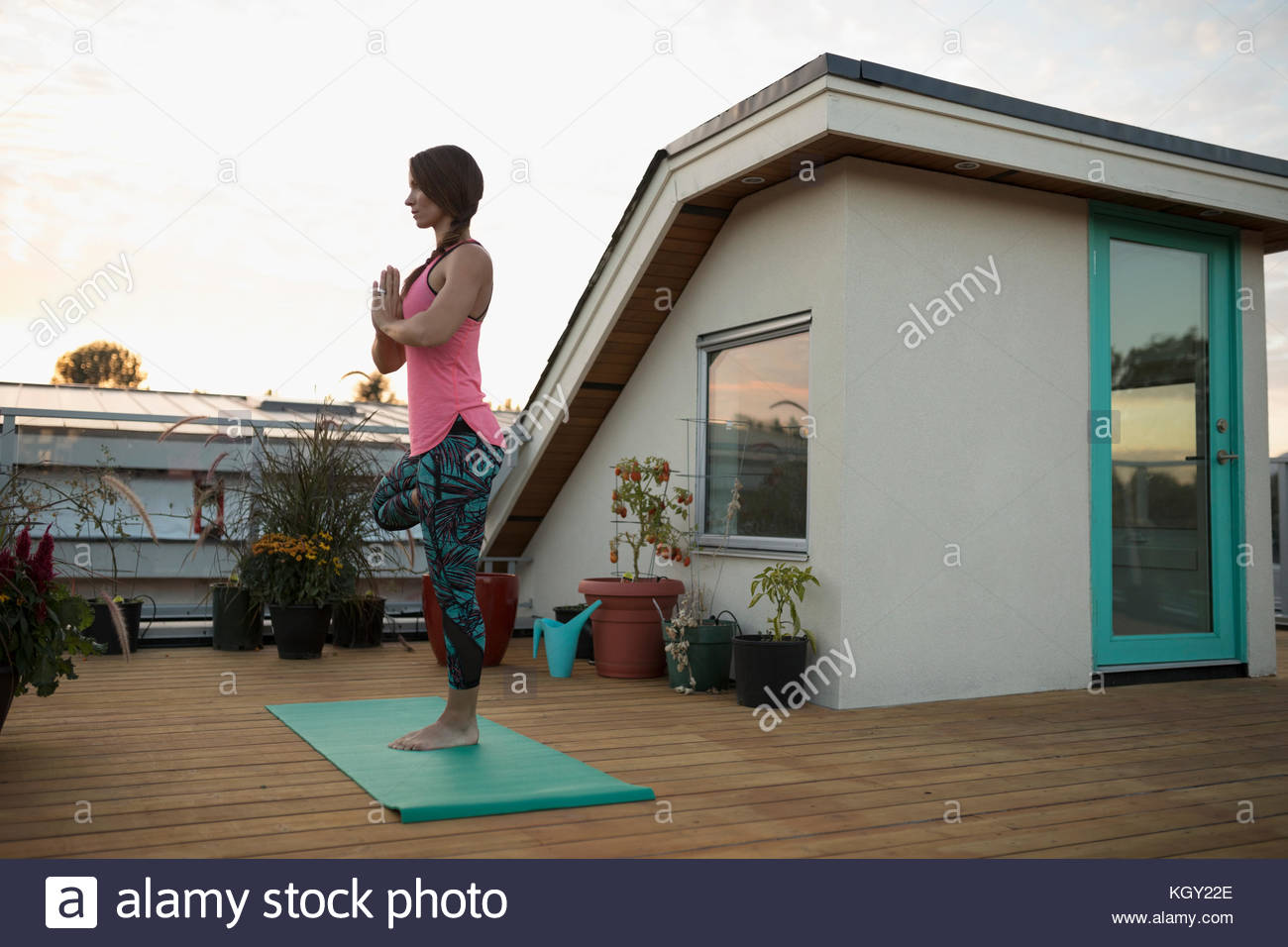 Serene woman standing in yoga tree pose with hands at heart center on yoga mat on deck patio - Stock Image