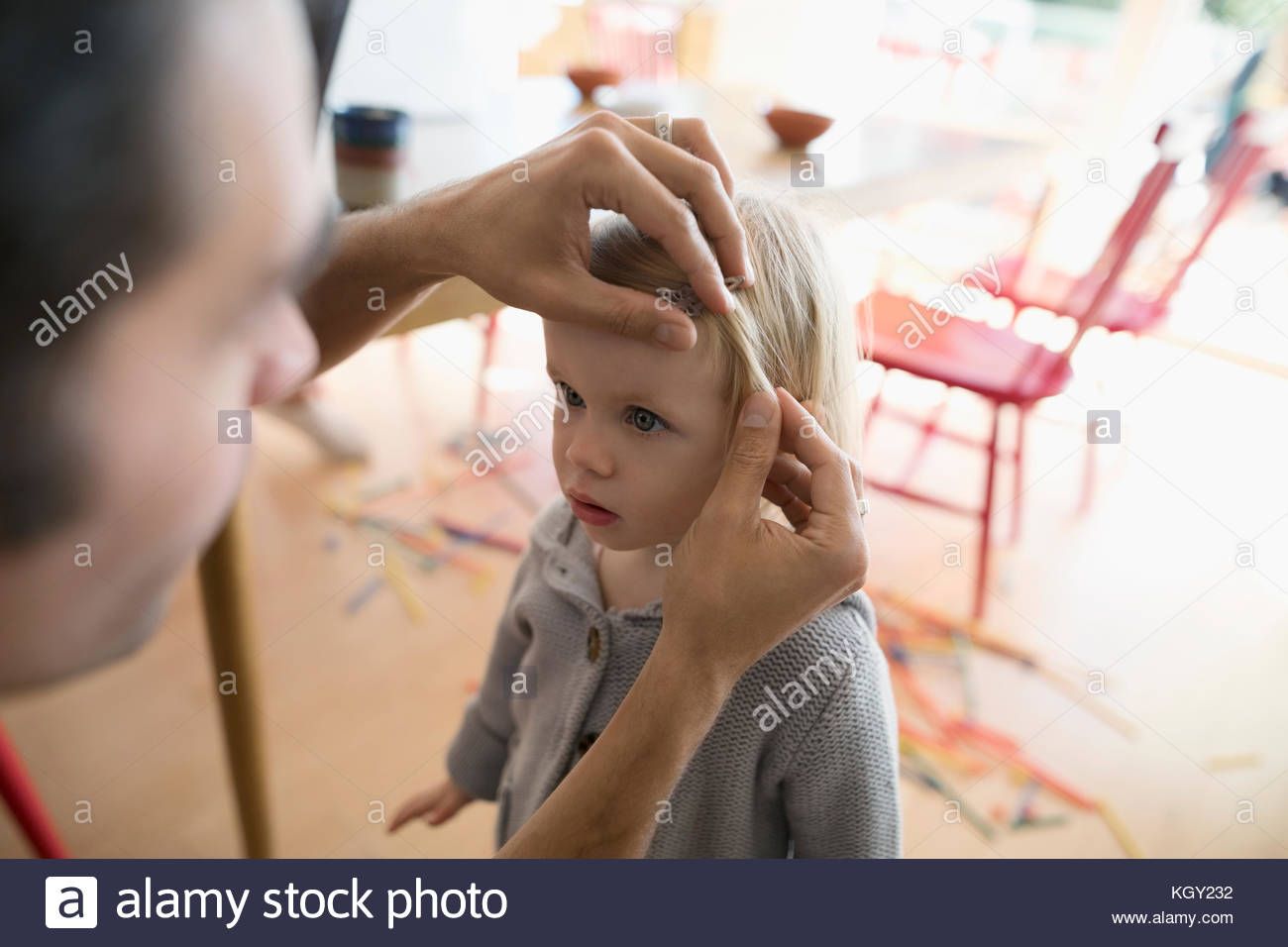 Father fixing toddler daughters hair - Stock Image