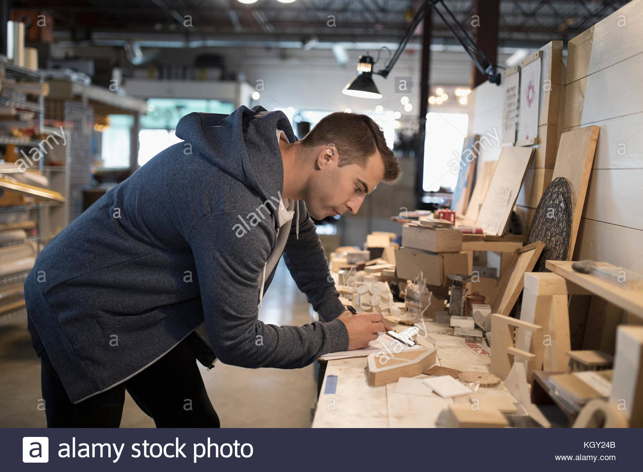 Focused male craftsman with clipboard and wood pieces in workshop - Stock Image
