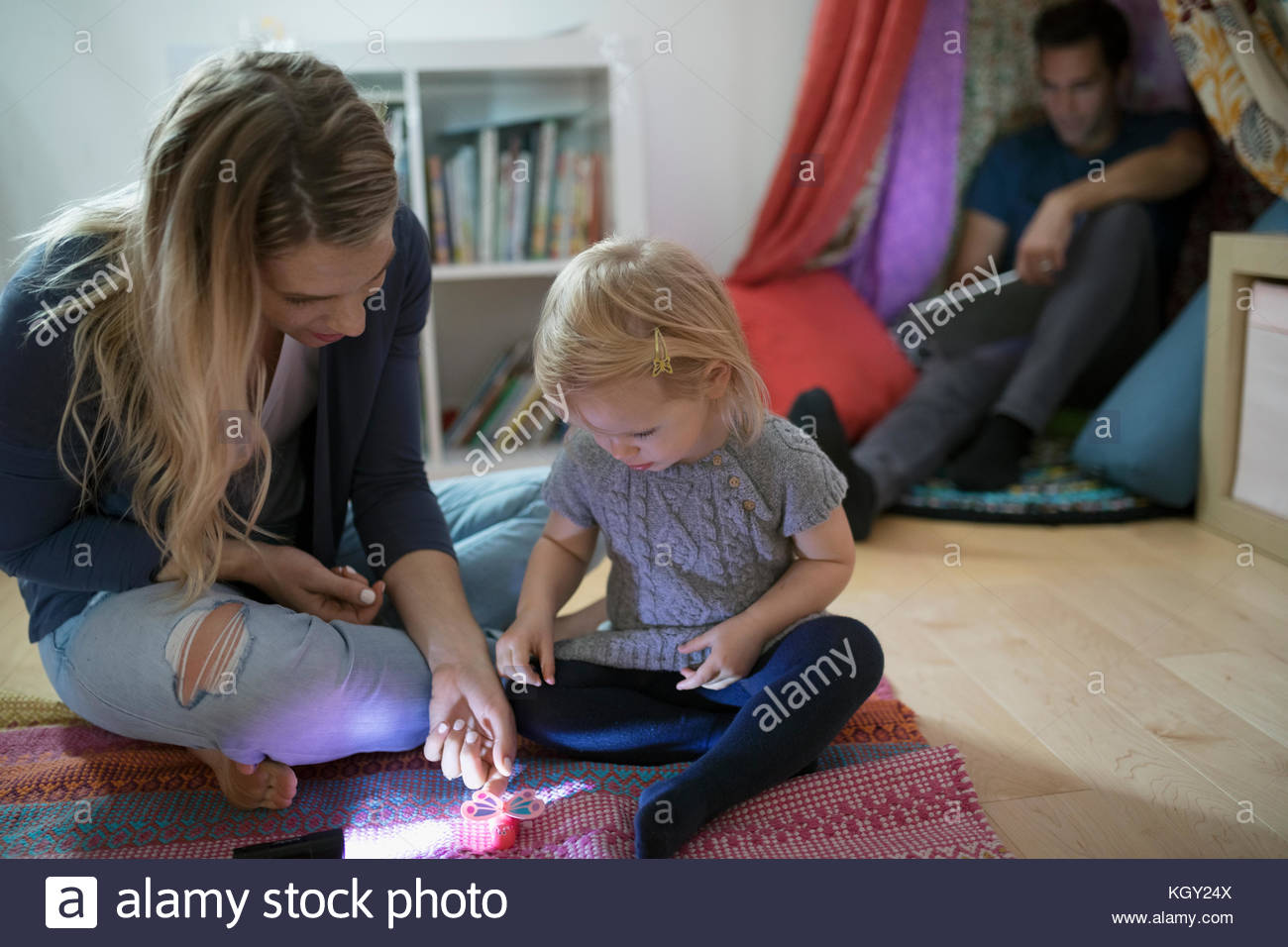 Blonde mother and toddler daughter playing with toy on bedroom floor - Stock Image