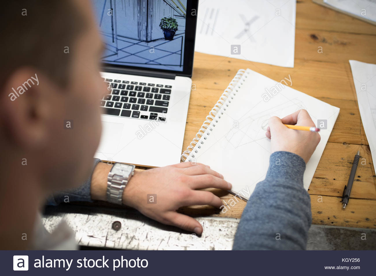Over the shoulder view male architect sketching in notebook at laptop - Stock Image