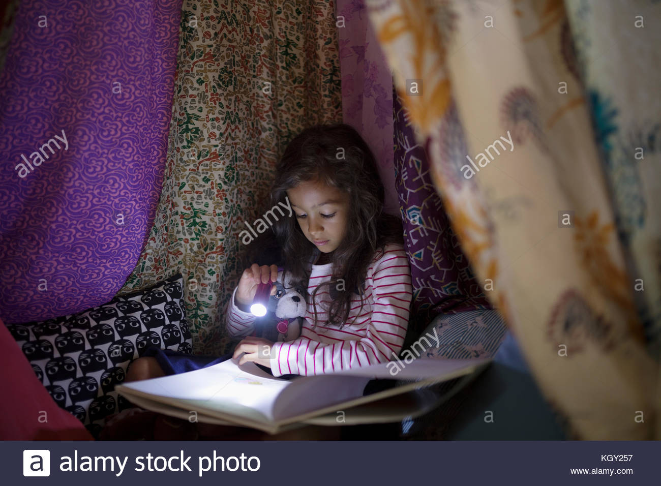 Girl with flashlight reading bedtime story in tent at night - Stock Image