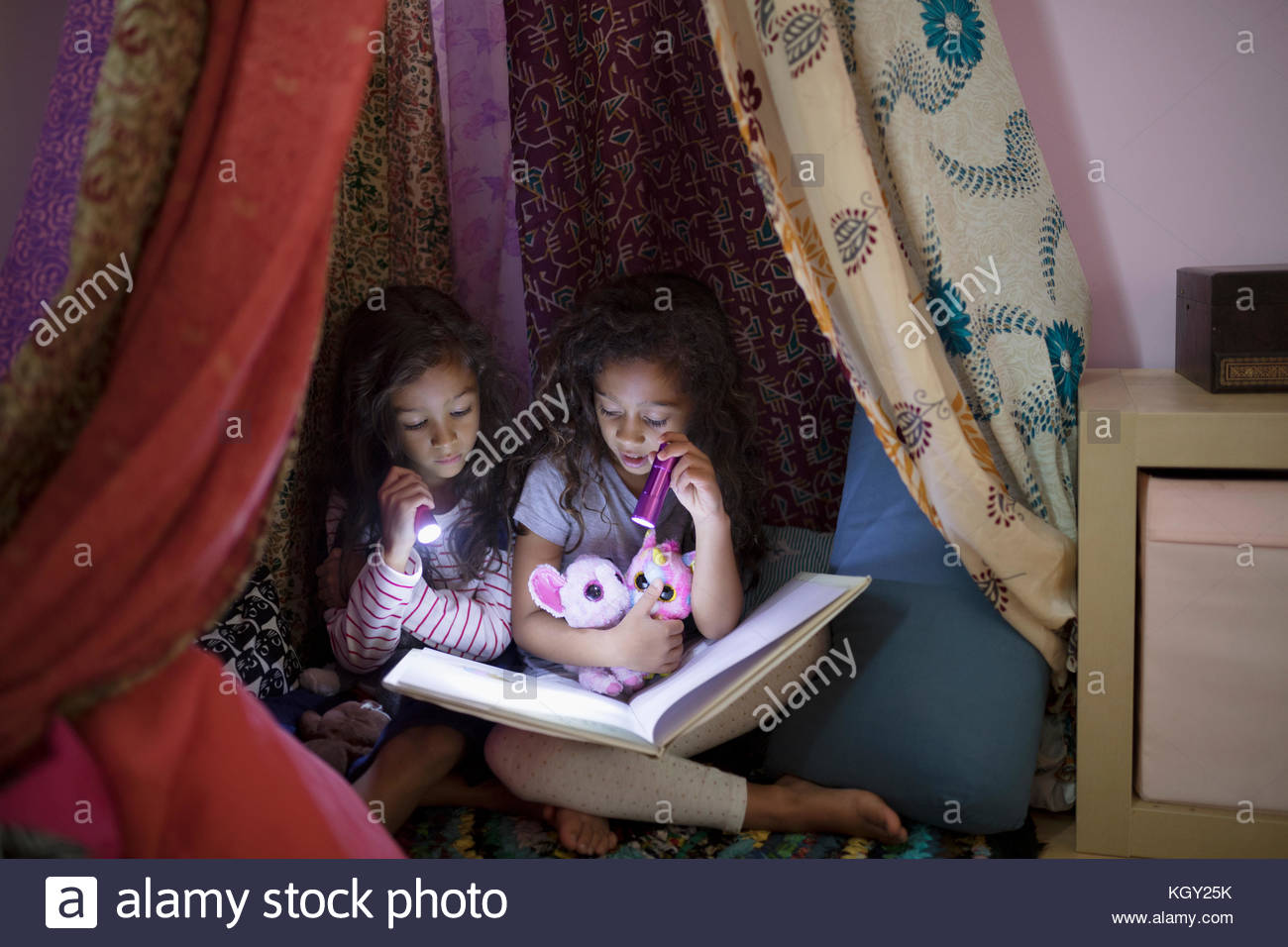Girl sisters with flashlights reading bedtime story in tent at night - Stock Image