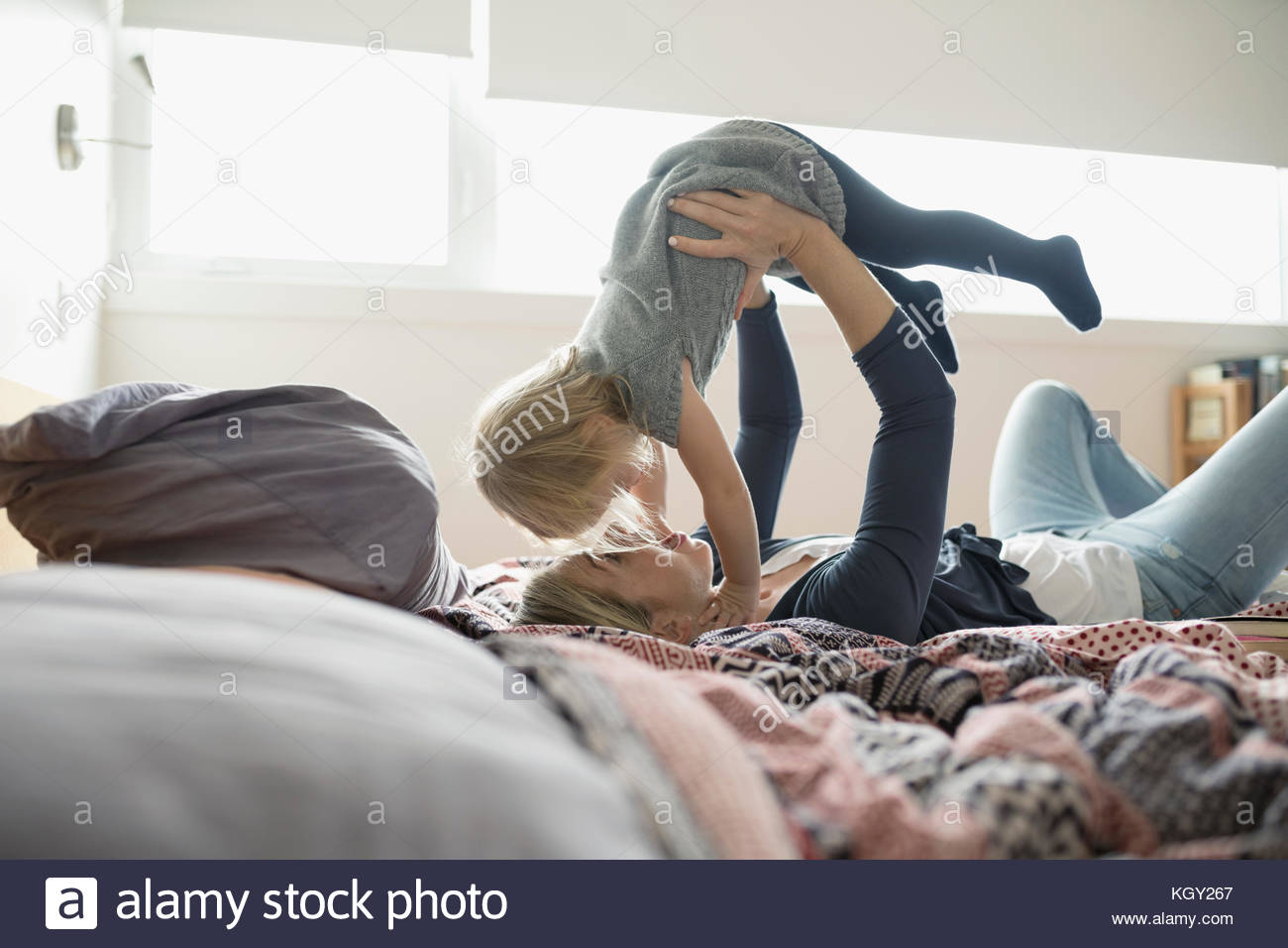 Affectionate mother holding daughter overhead on bed - Stock Image