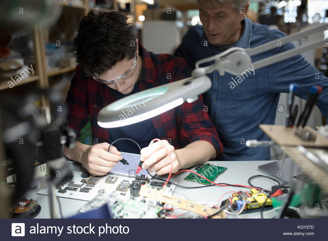 Focused male engineers using soldering iron, assembling electronics circuit board in workshop - Stock Image