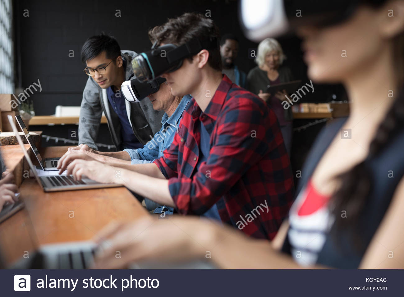 Designers testing and programming virtual reality simulator glasses at laptops in office - Stock Image