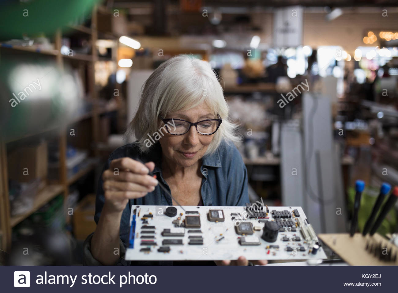 Senior female engineer assembling electronics circuit board in workshop - Stock Image