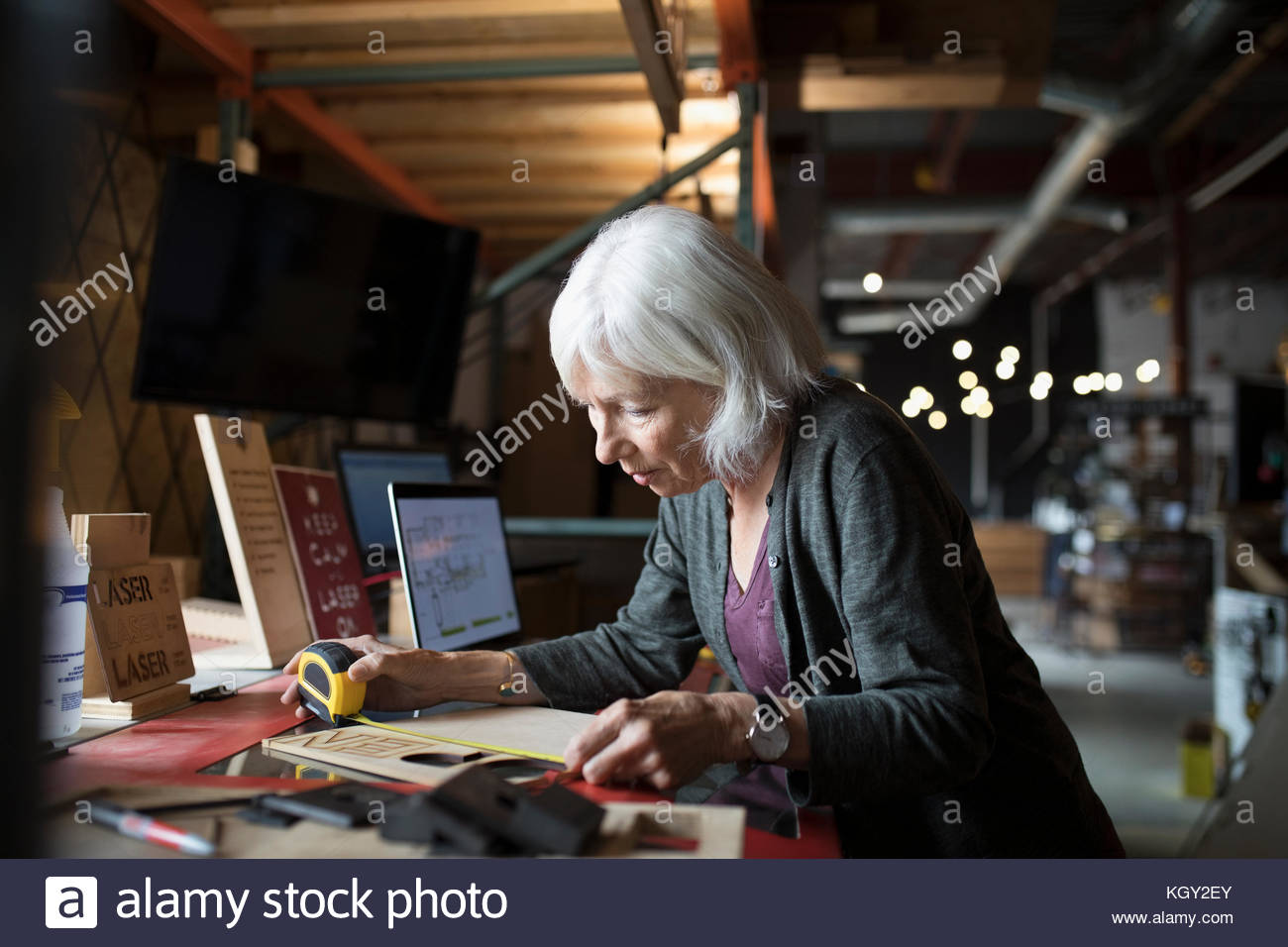 Senior female machinist measuring laser cut sign on laser cutter in workshop - Stock Image