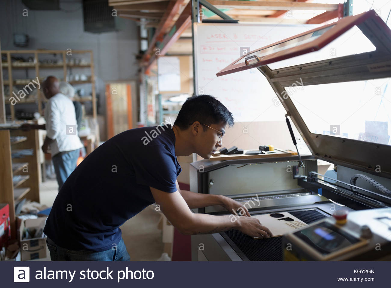 Male engineer using laser cutter in workshop - Stock Image