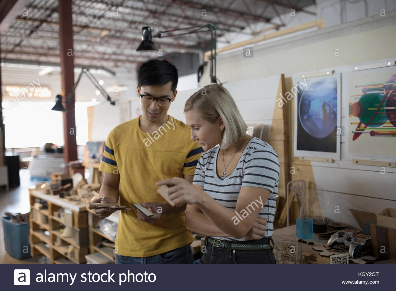 Small business owner craftspeople examining pieces in workshop - Stock Image