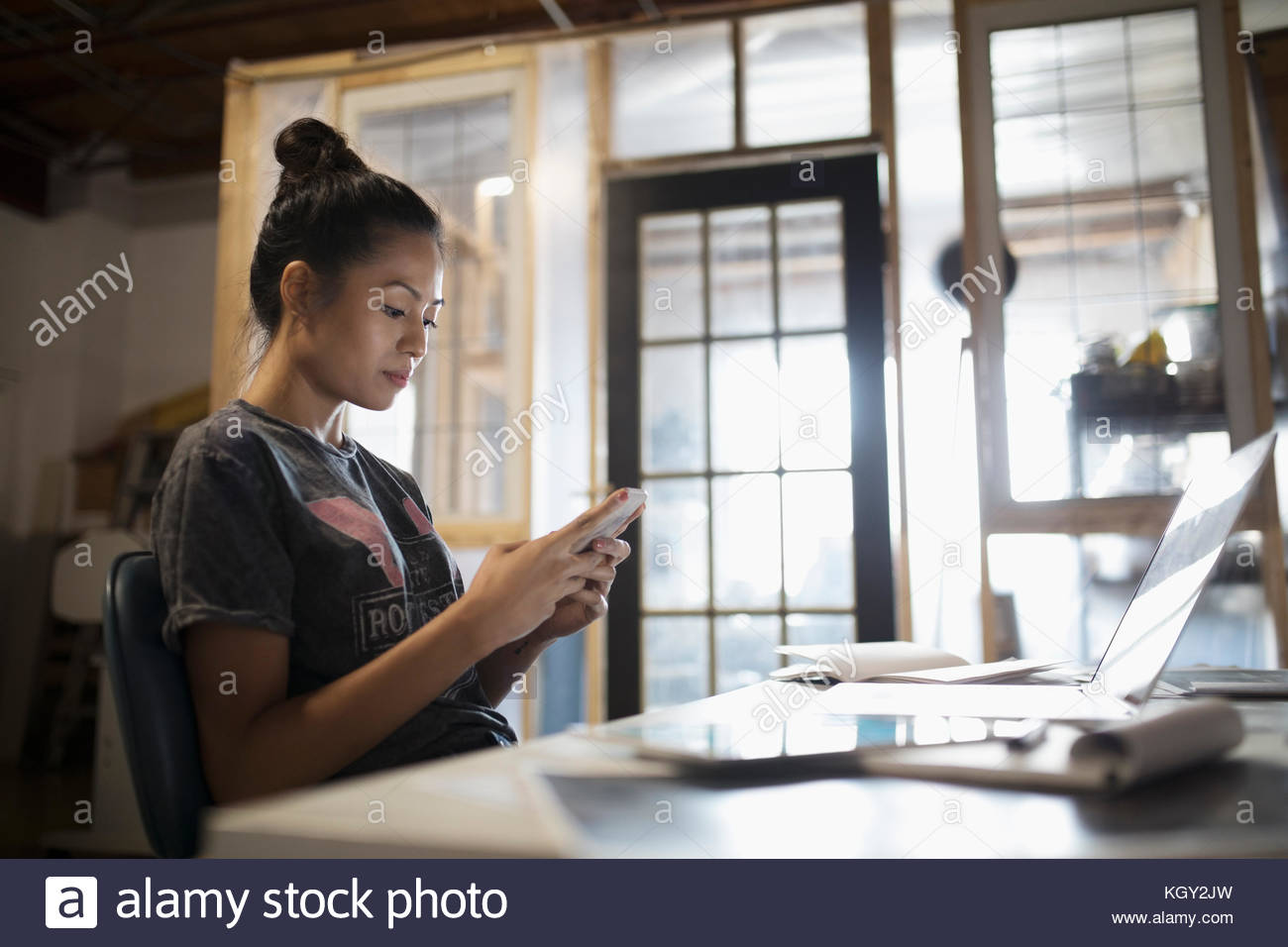 Young woman texting with smart phone at laptop in office - Stock Image