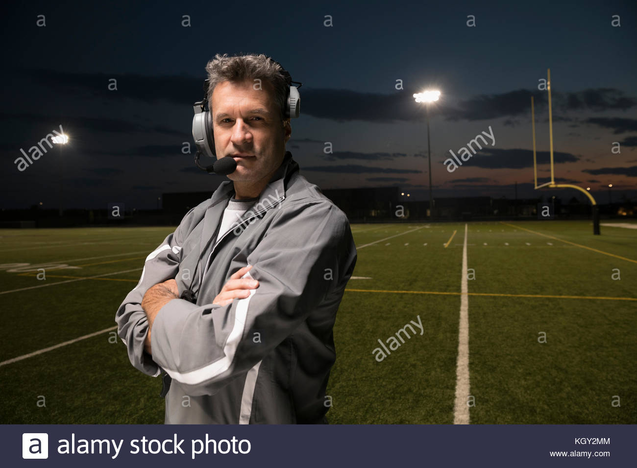 Portrait confident, tough high school football coach wearing headset on football field at night - Stock Image
