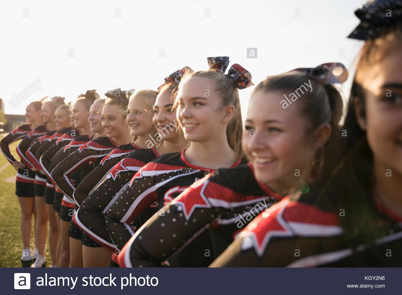 Teenage girl high school cheerleading team poised, smiling and standing in a row looking away - Stock Image