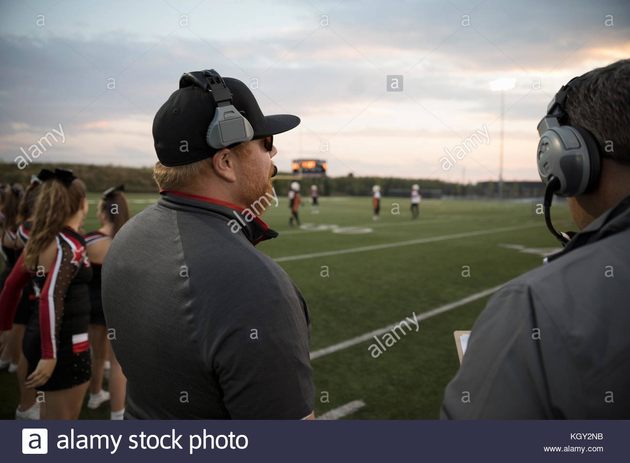 High school football coaches with headsets watching football game on sideline of football field - Stock Image
