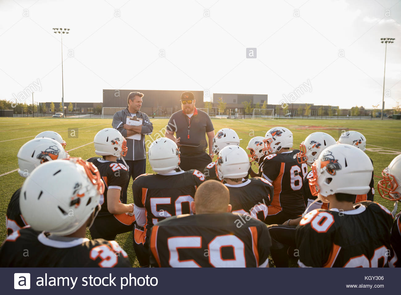 Coaches talking to teenage boy high school football team before game on sunny football field Stock Photo