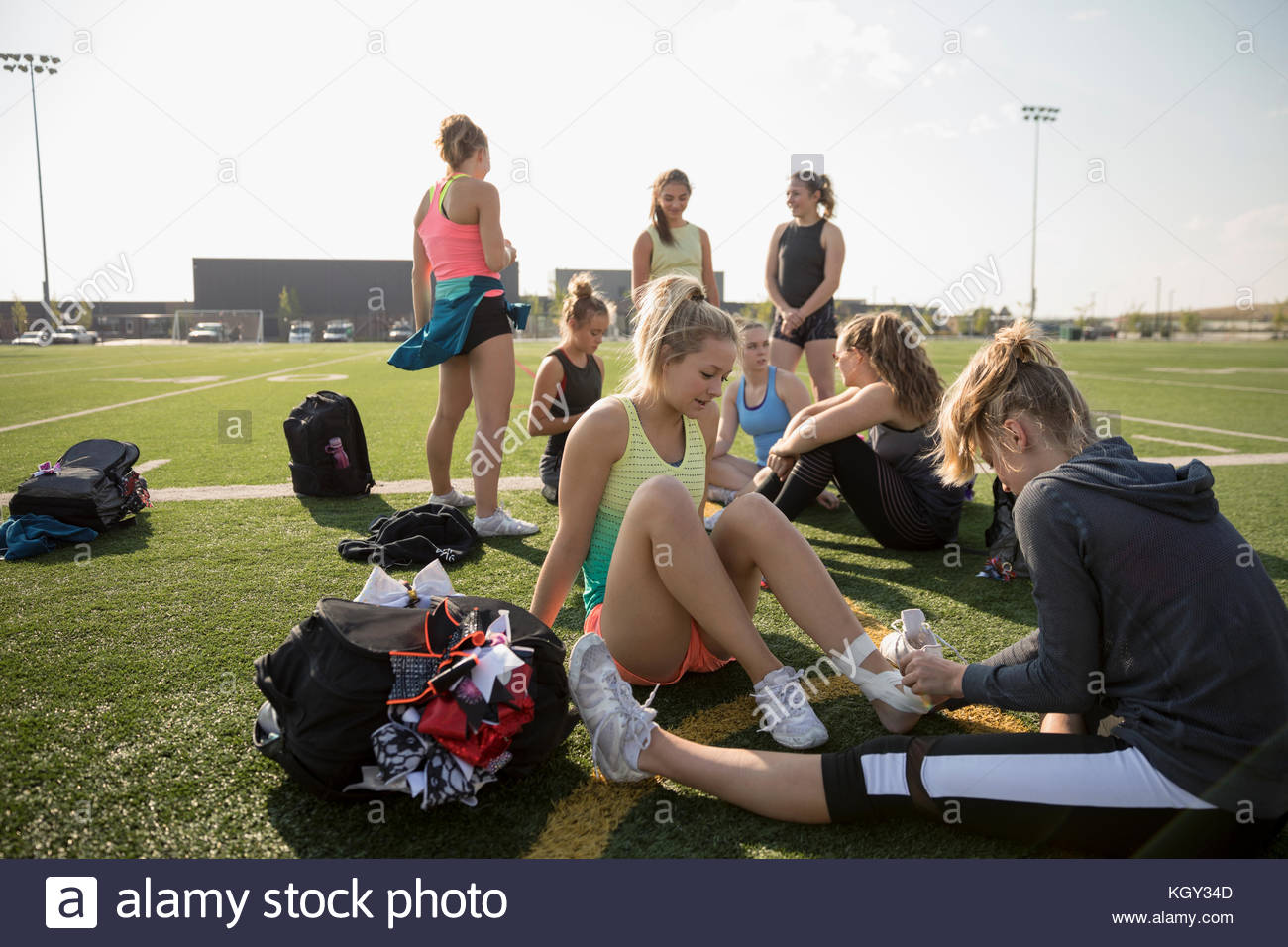Teenage girl high school cheerleading team taping foot and ankle with tape on sunny football field - Stock Image