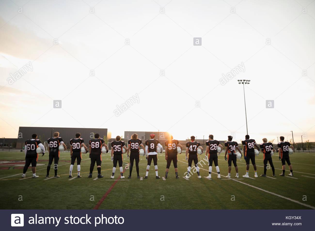 Rear view teenage boy high school football team standing in a row on football field - Stock Image