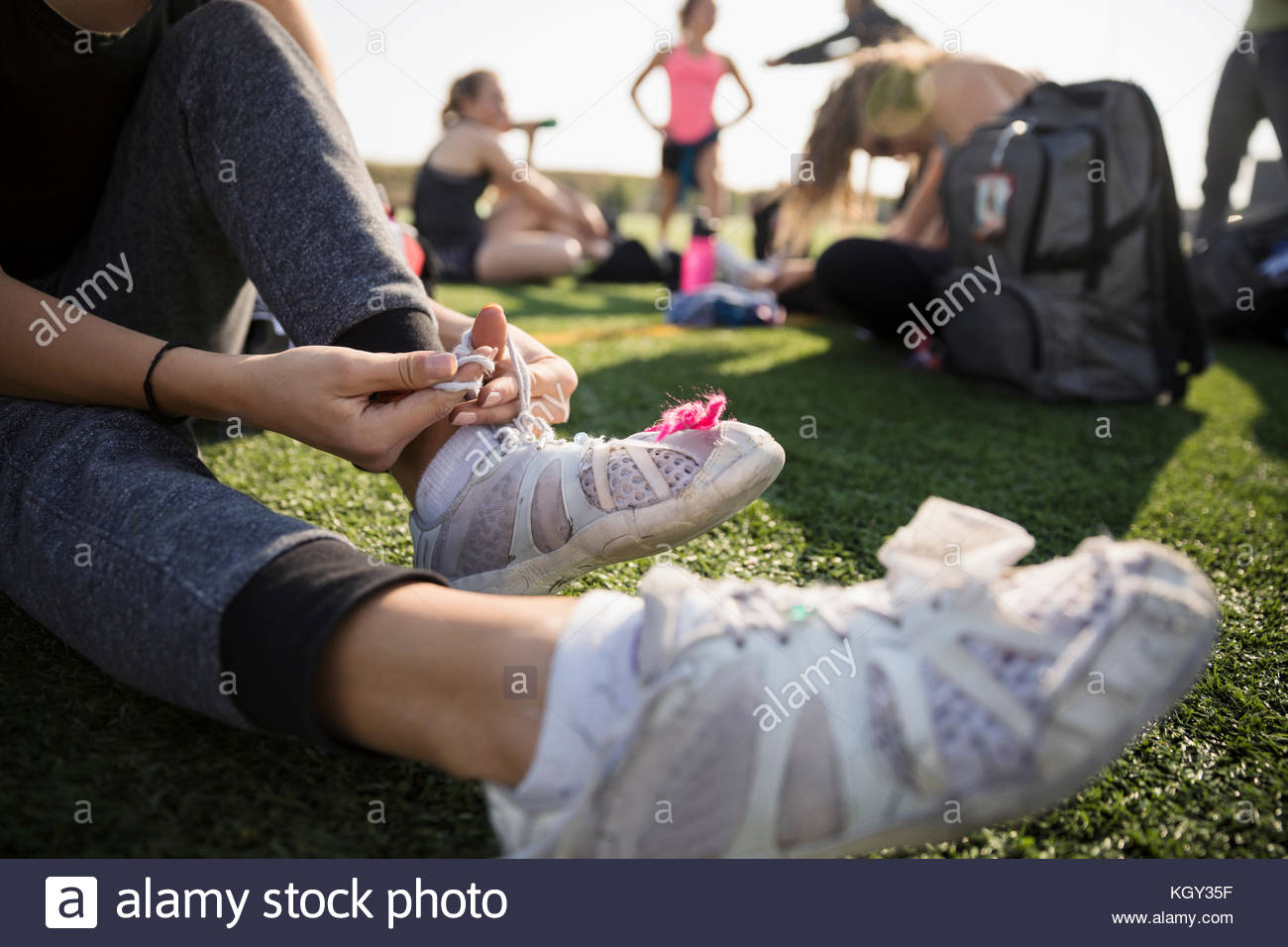 Teenage girl high school cheerleader tying shoes on football field - Stock Image