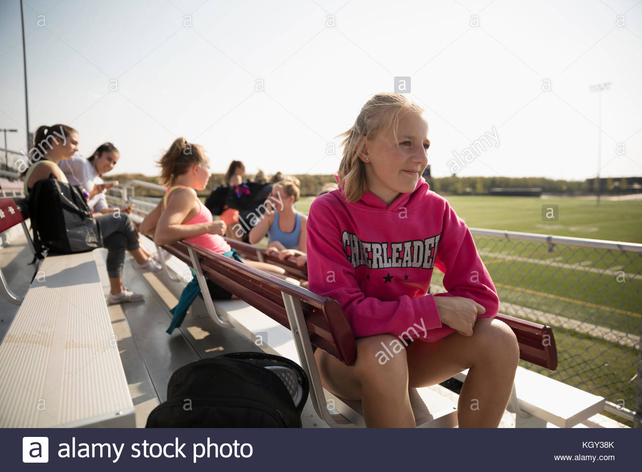 Teenage girl high school cheerleader sitting and looking away on sunny bleachers - Stock Image