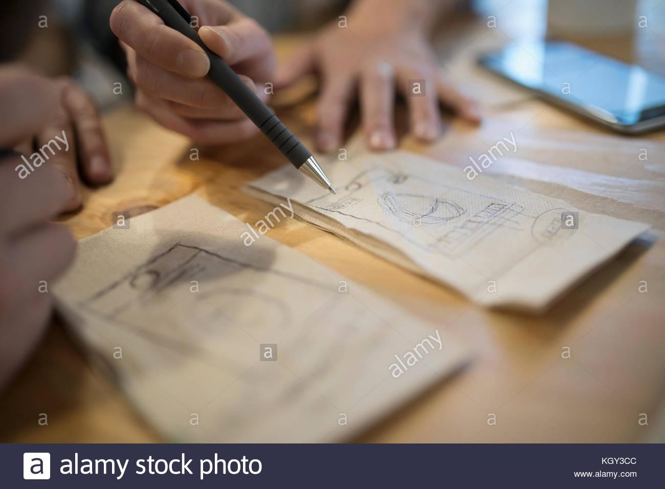 Close up creative designers brainstorming ideas on napkins - Stock Image