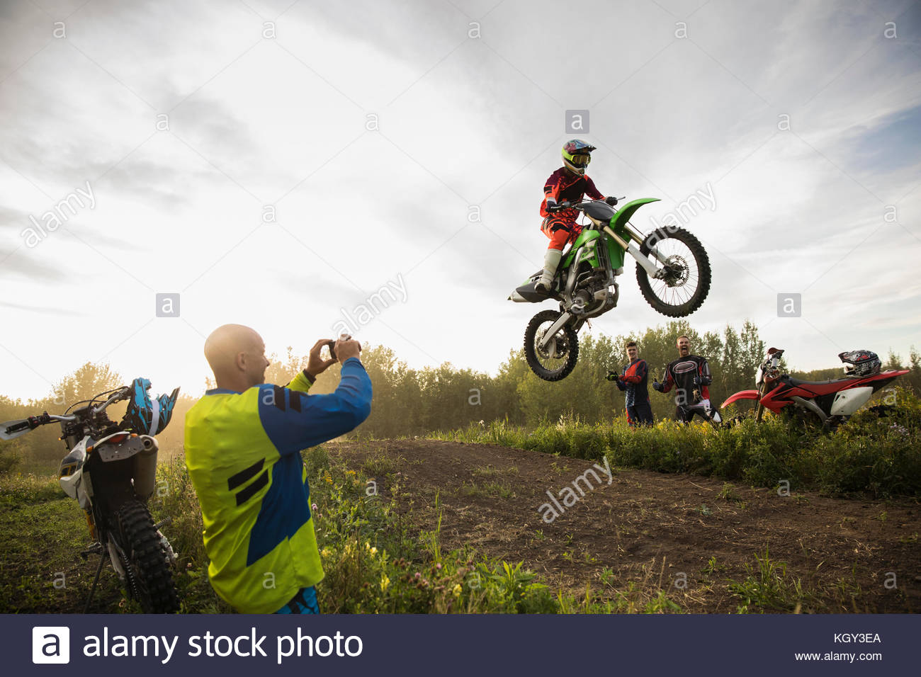 Man with camera phone photographing friend doing motorbike stunt jump on rural dirt road - Stock Image