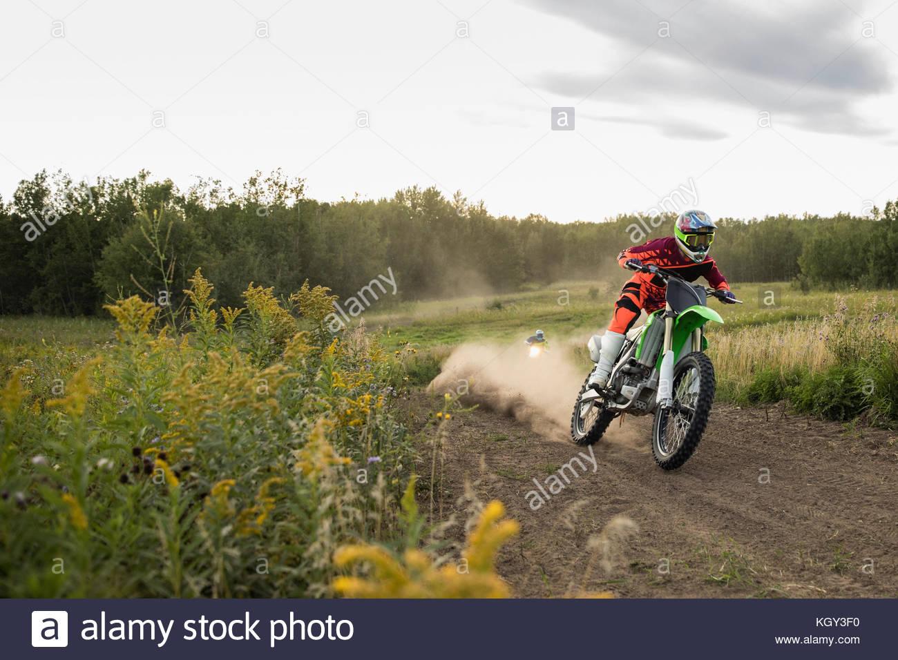 Man racing motorbike on rural dirt road - Stock Image