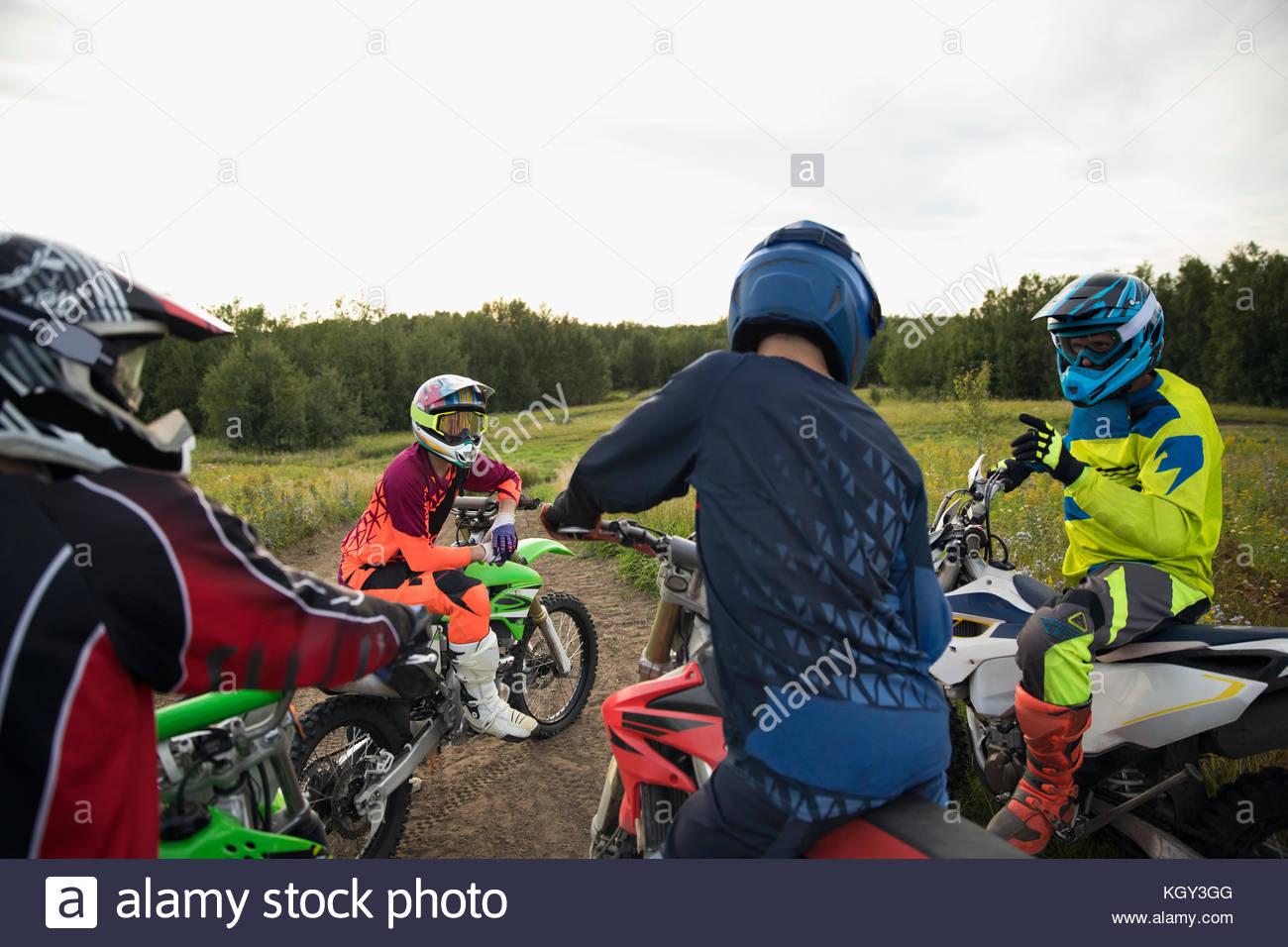 Male friends on motorbikes talking - Stock Image