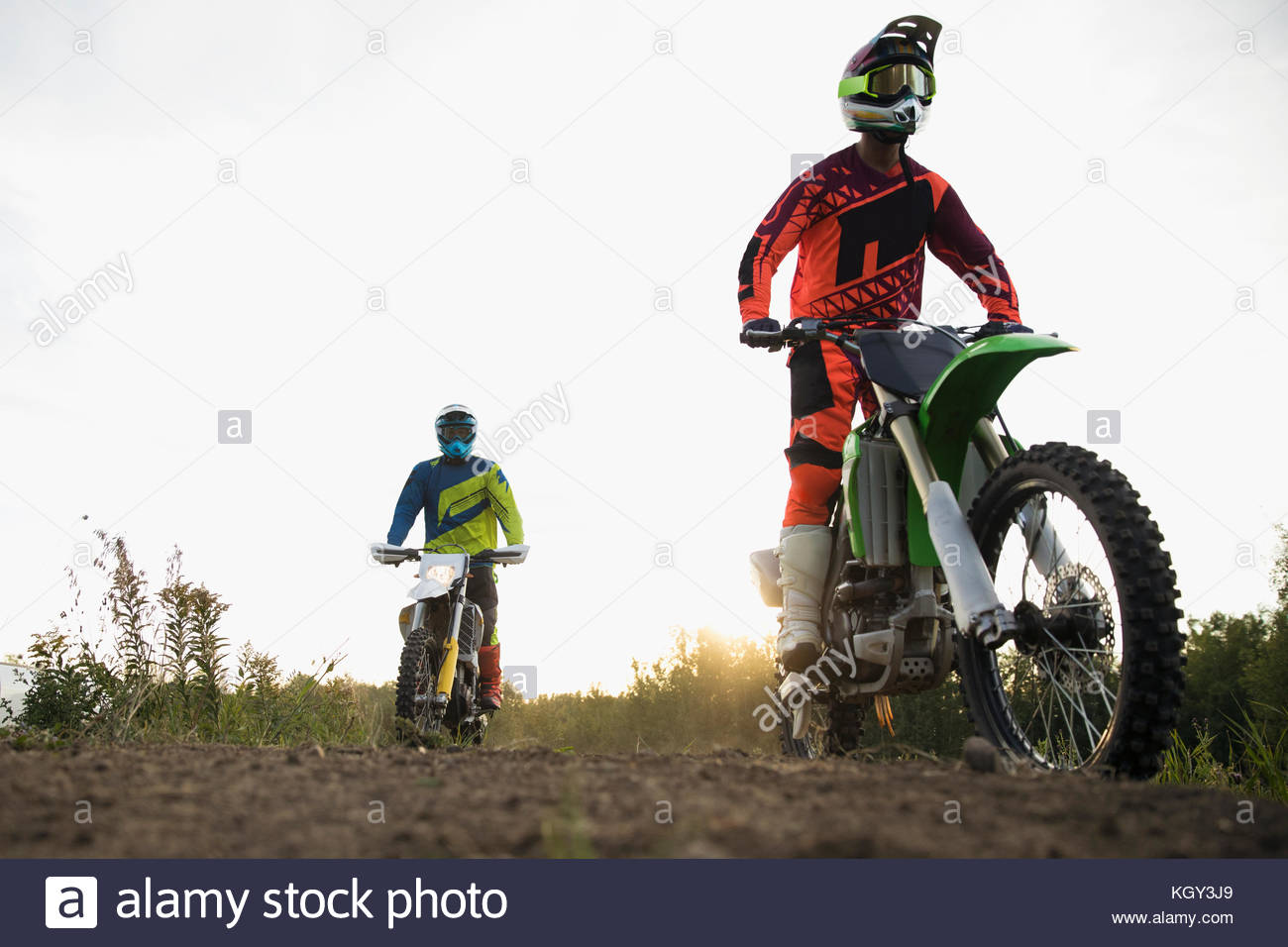 Male friends riding motorbikes on dirt road - Stock Image