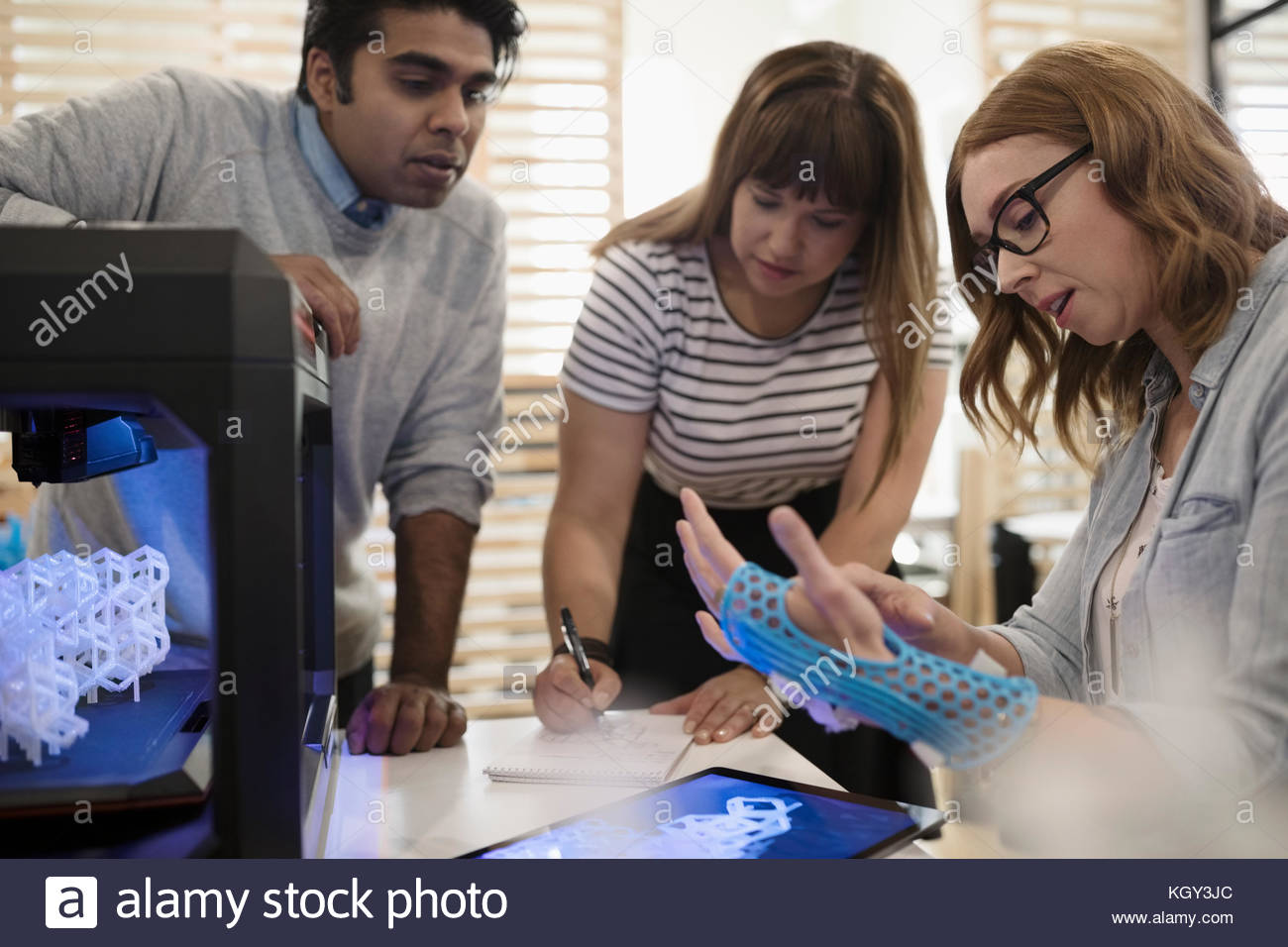 Designers examining glove prototype at 3D printer in office - Stock Image