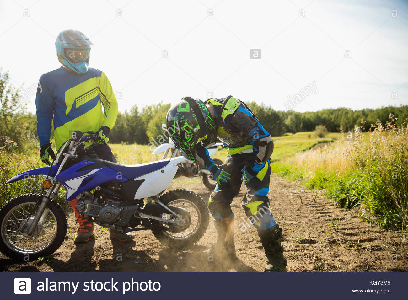 Father helping daughter with motorbike on sunny rural dirt road - Stock Image