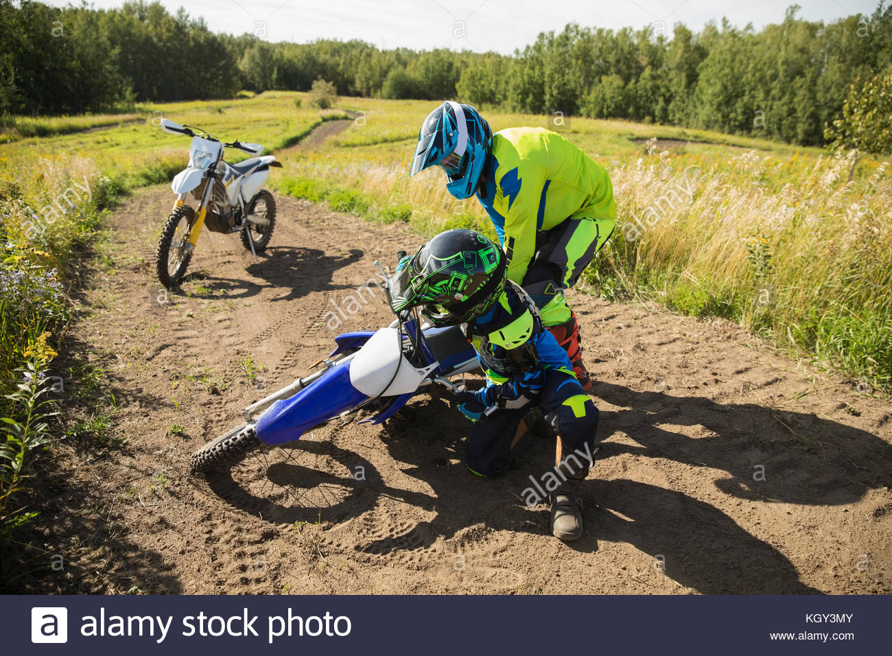Father helping daughter falling on motorbike on sunny dirt road - Stock Image
