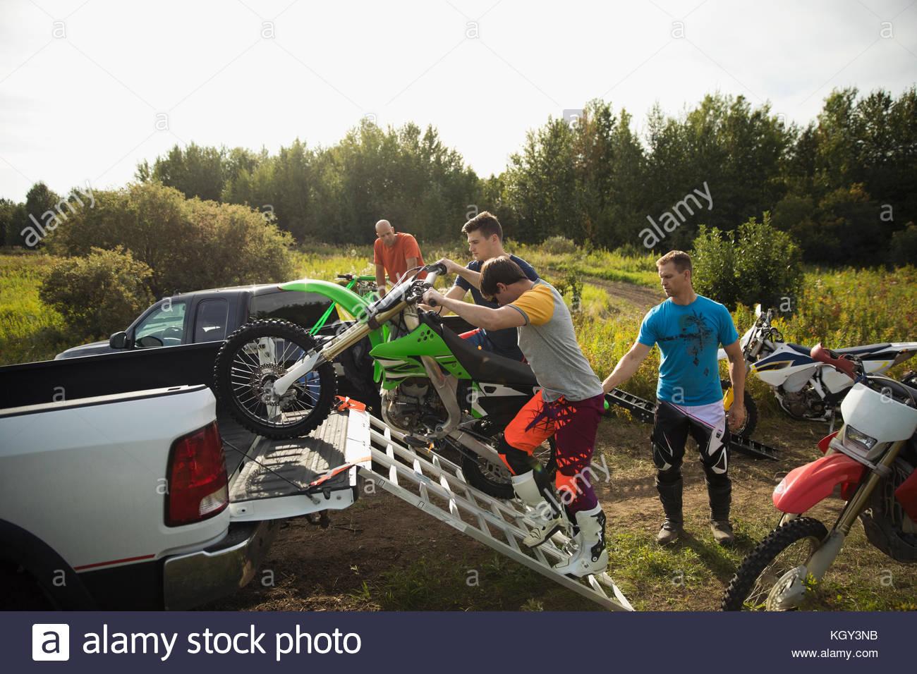 Men loading motorbikes onto truck - Stock Image