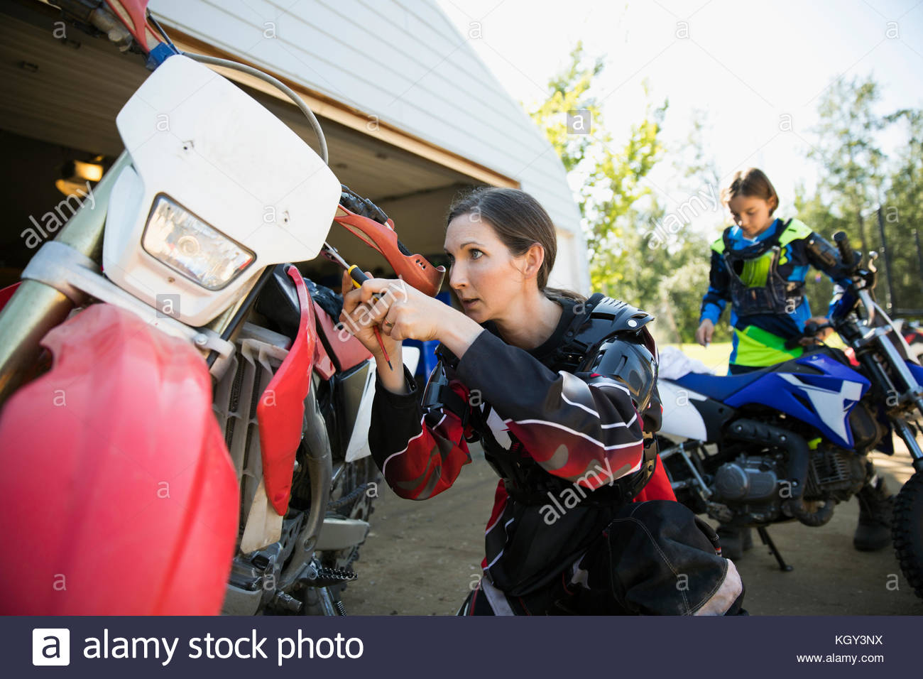 Mother and daughter fixing motorbike in driveway - Stock Image