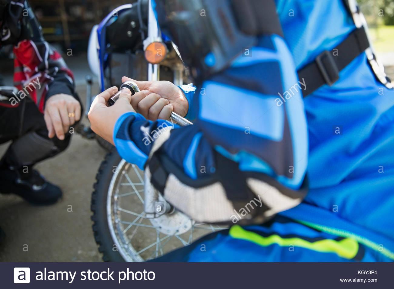 Girl using socket wrench, fixing motorbike Stock Photo