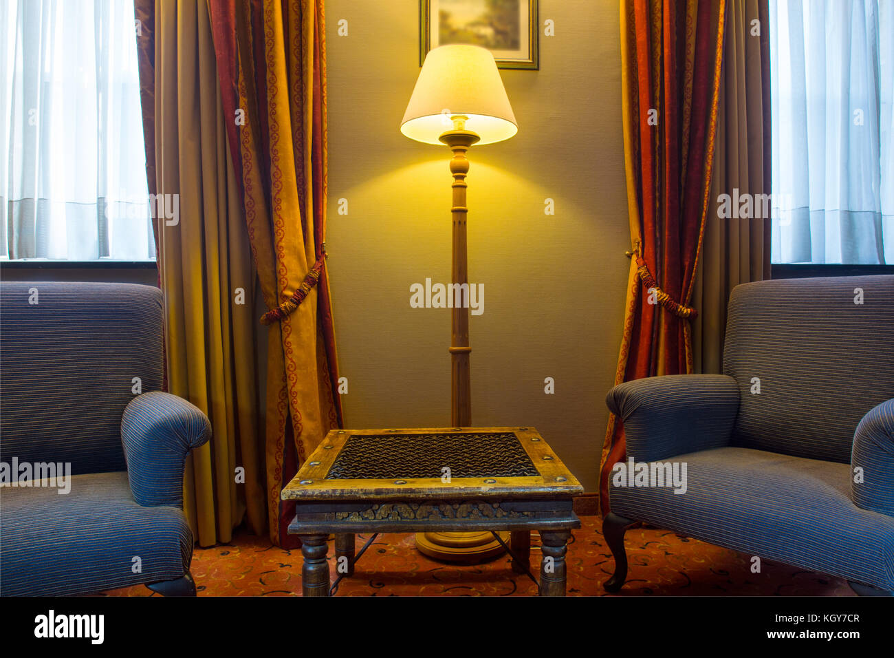 Traditional European Style Room With Chairs And Side Stand In A Living Floor Lamp Fully Decorated Windows Showing Warm Inviting