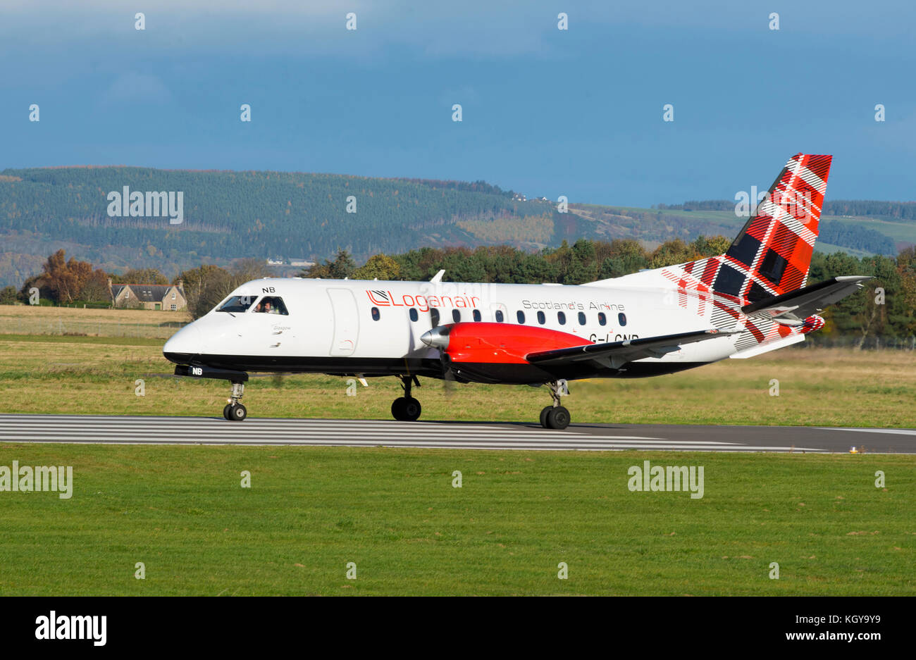 the Loganair Saab 340 in its Scottish Tartan Liver leaving Inverness Airport for its daily flight across to Stornoway - Stock Image