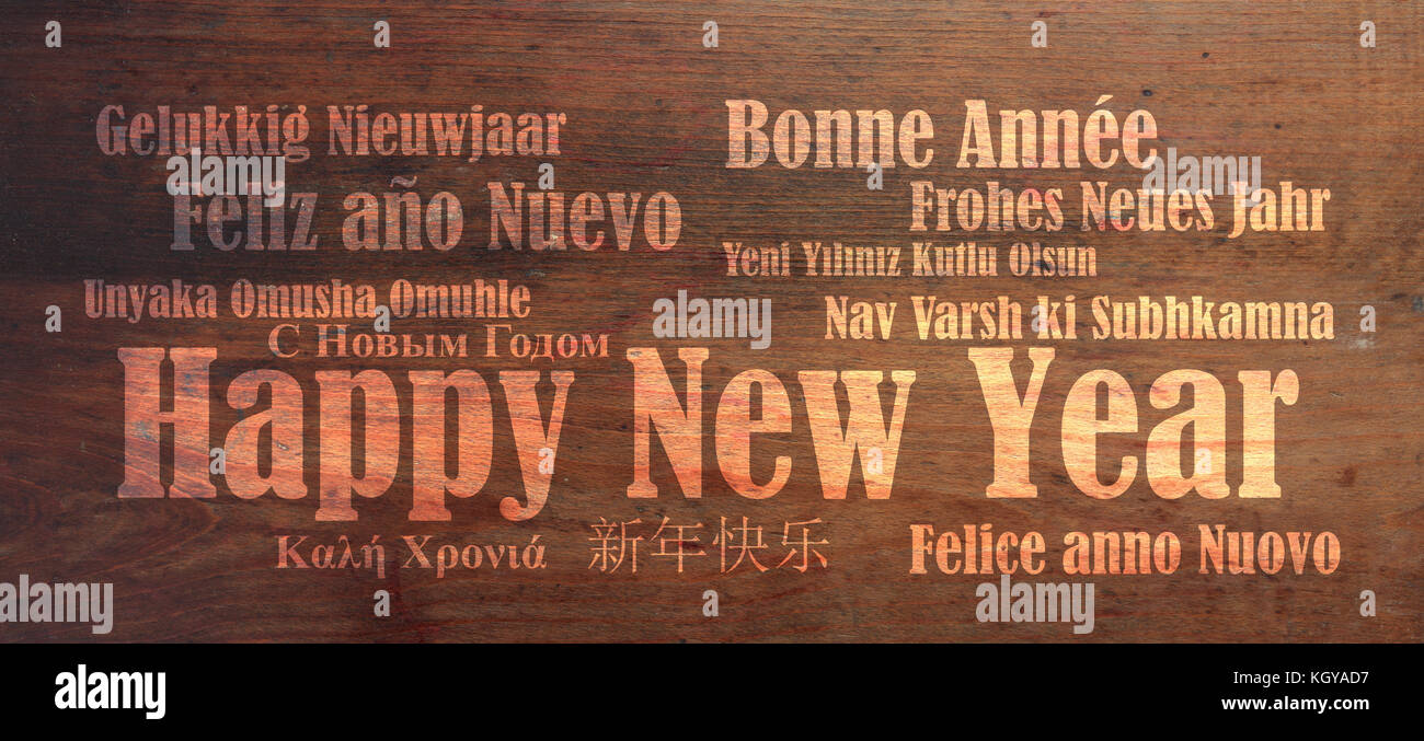 Happy new year wish in many languages on wooden background - Stock Image