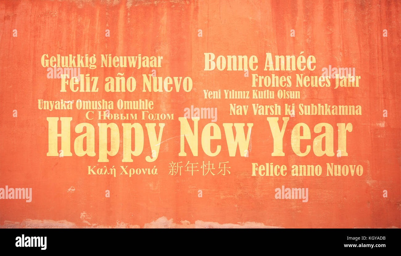 Happy new year wish in many languages on stucco painted wall background - Stock Image