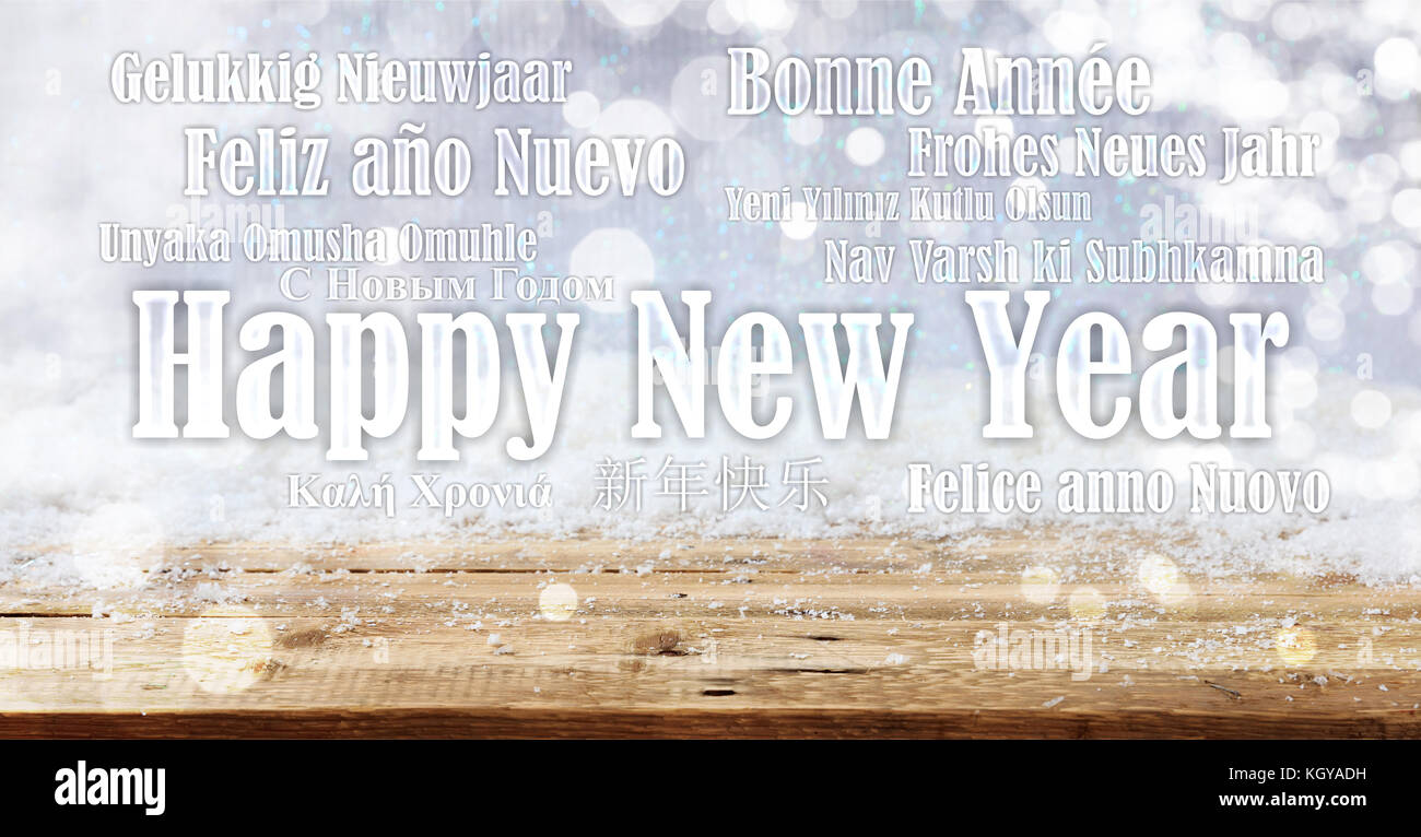 Happy new year wish in many languages on snowy background - Stock Image
