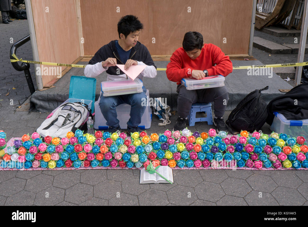 A Chinese American young man makes colorful origami flowers and instructs his friend in origami. At Union Square - Stock Image