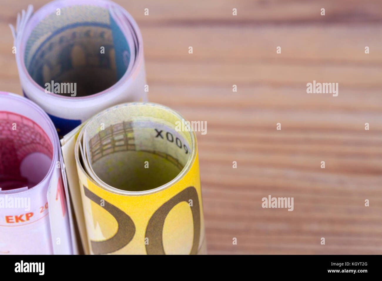 Close up view of bankroll cash euro banknotes in finance concept on wooden background. - Stock Image