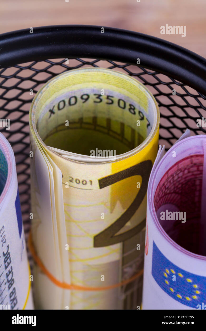 Bankroll cash euro banknotes in garbage basket focused on consuming in finance concept on wooden background. - Stock Image