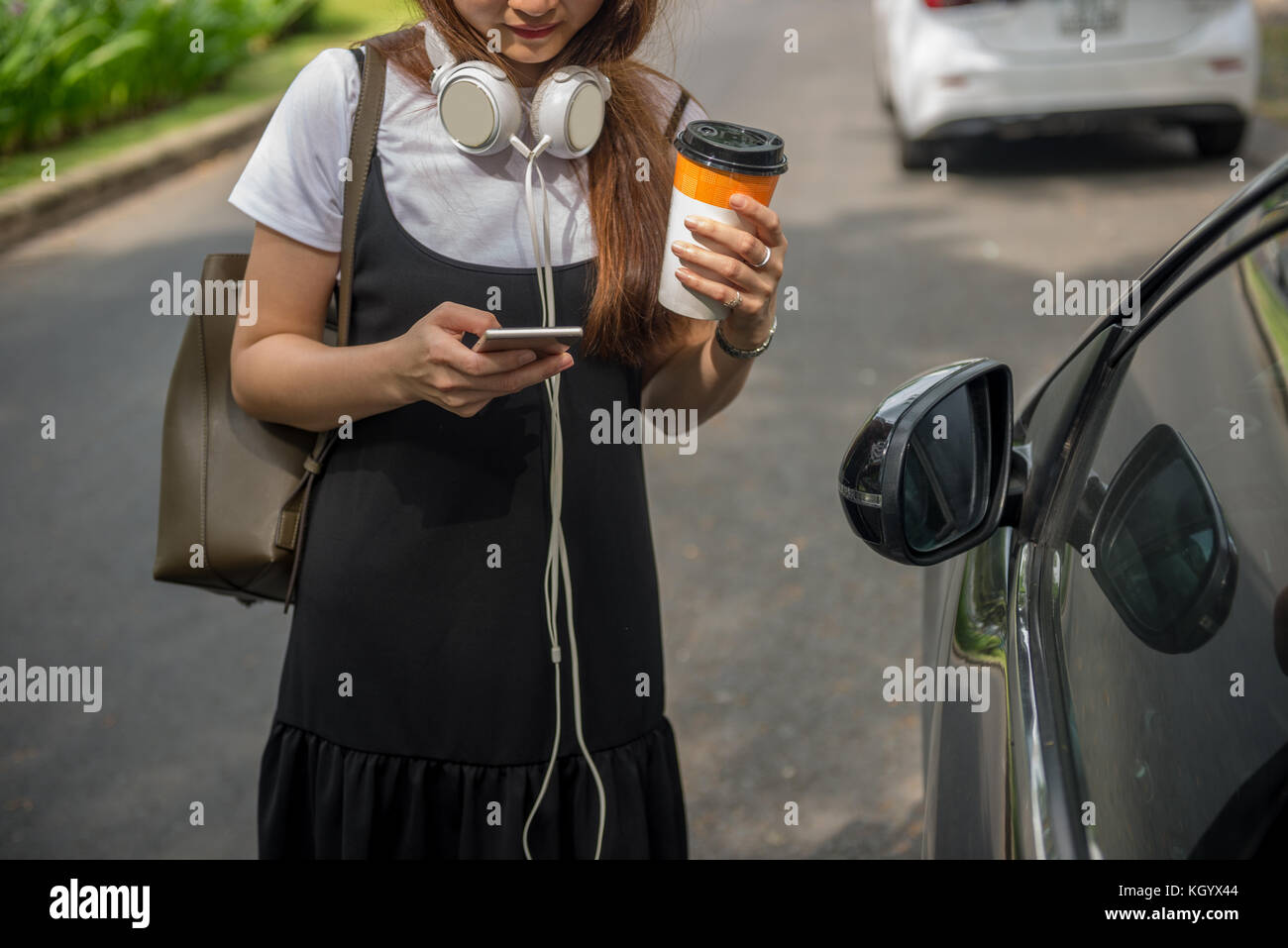 Modern woman texting on smart phone outdoor - Stock Image
