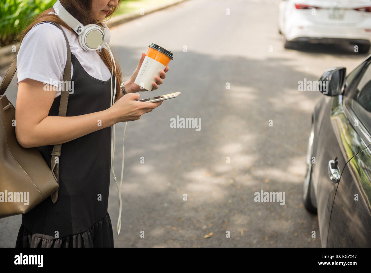 Modern woman holding coffee and checking email on smart phone - Stock Image