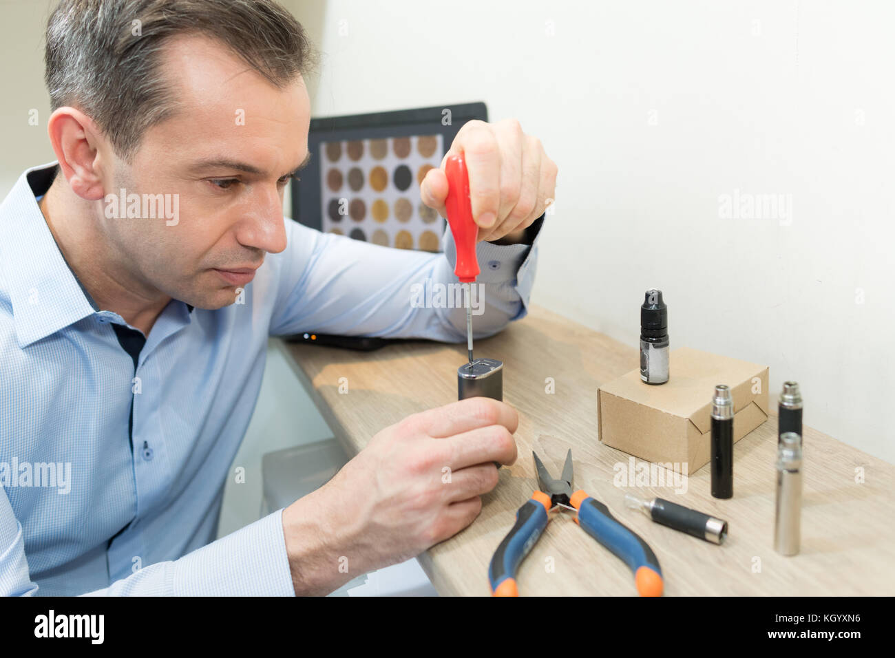 man setting up electronic cigarette coil - Stock Image